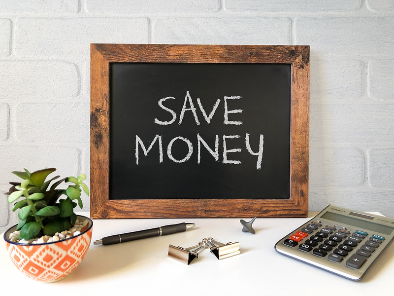 """Black Board on a desk with """"Save Money"""" by getting Dental Care with Kriebel Dental in Costa Rica"""